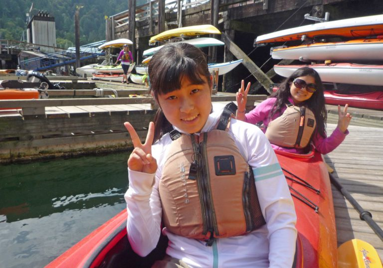 Two women sitting in a kayak on the dock holding their hands showing peace signs
