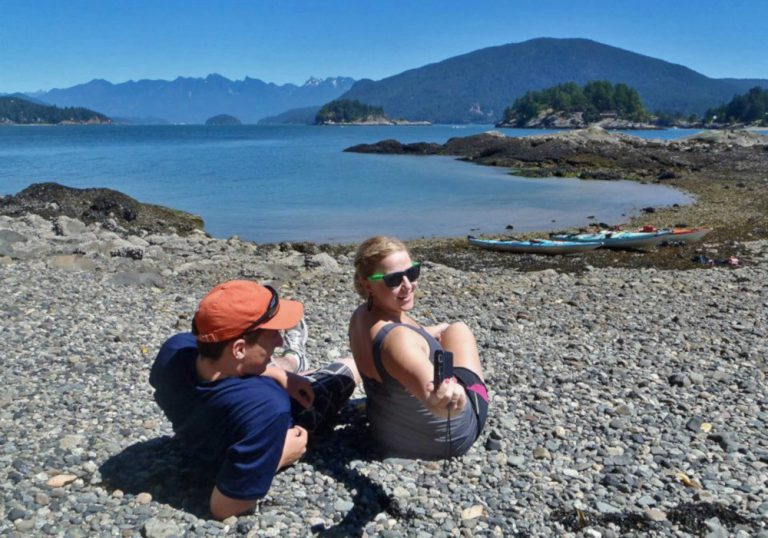 Man and a woman sitting on a rocky beach with kayaks on the shore. Several islands and mountains in the background.