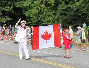 Man in old white naval suit and woman in a red dress carrying a Canadian Maple Leaf flag at the head of a parade. People can be seen sitting on the side of the street.
