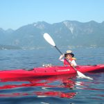 Child kayaking in a red kayak with mountains in the backgroun