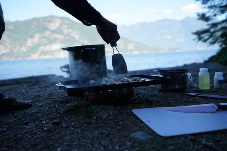 Person cooking eggs on a skillet on a camping stove on a beach. Island and mountains are shown in the background.