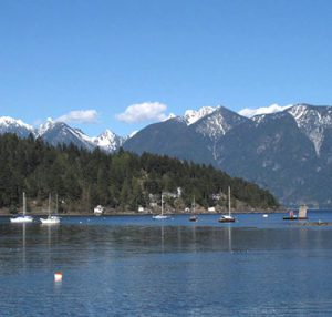 Bay with several moored yachts with a wooded shoreline and mountains in the background
