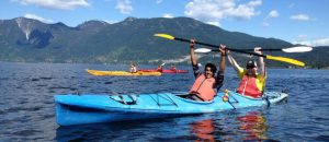 Two men in a kayak holding paddles in the air. 2 more kayaks and mountains are in the background.