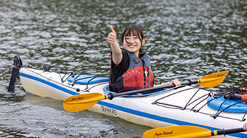 Woman in a kayak giving the thumbs up sign