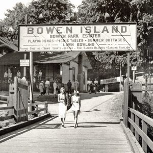 Black and white picture of two women walking on a pier with a pavilion in the background. There is a sign above welcoming them to Bowen Island - Park Estates circa 1948