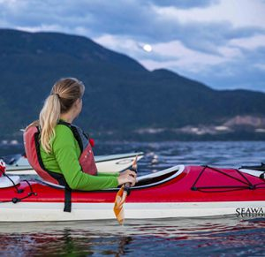 Woman in a red kayak looking towards mountains with the full moon rising above it