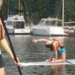 Two women on stand up paddle boards, one doing yoga while the other watches