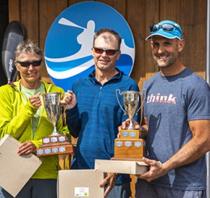 Man and a woman holding a trophy. Next to them a man holding another trophy. In the background is the Bowen Island Sea Kayaking Logo