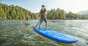 Man on blue stand up paddle board with wooded shoreline and other stand up paddle boarders in the background