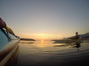View down the side of a kayak looking towards the sun setting in the distance. Another man is in a yellow kayak.