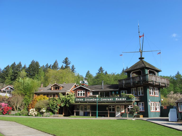 Wooden 2 story building with ships mast on the upper right. Sign says 'Union Steamship Company Marina'