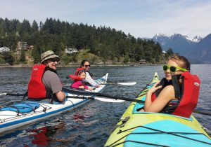 Family in two kayaks with wooded shore and mountains in the background