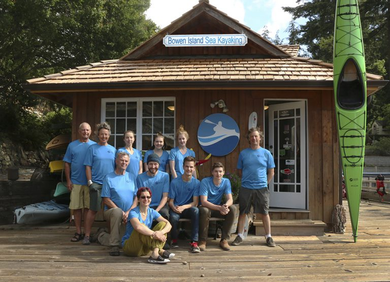Group of men and women standing in front of a wooden office (staff of Bowen Island Sea Kayaking)