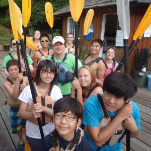 A dozen boys and girls standing on a dock in front of a wooden kayak office holding paddles upright