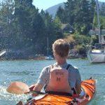 Boy in orange kayak viewed from the back