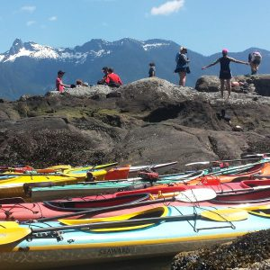 9 children on rocks with mountains in the background. Kayaks are on the shore in the foreground