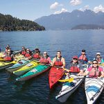 12 men and women in kayaks with islands and mountains in the distance
