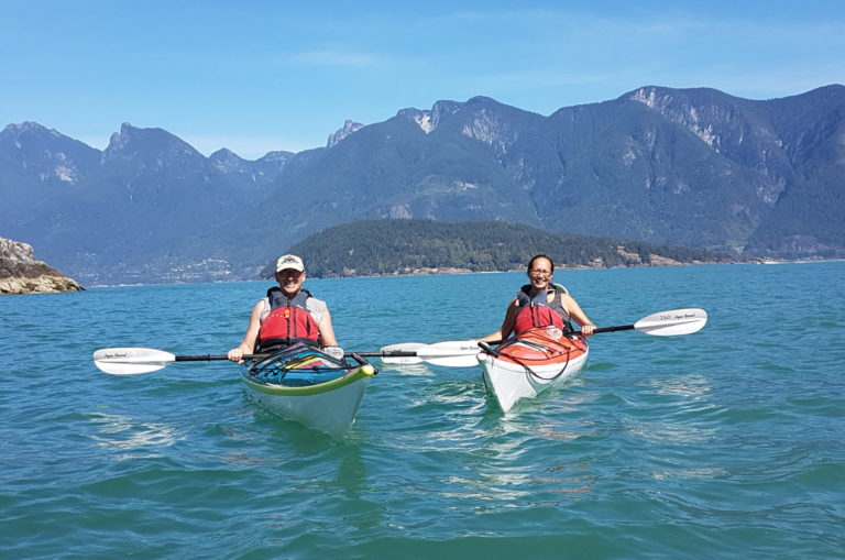 2 adults kayaking with mountain background