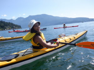 young girl smiling in yellow kayak