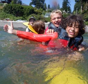 children playing on top of submerged kayak