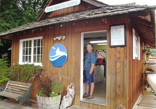 Man standing in the doorway to wooden office building